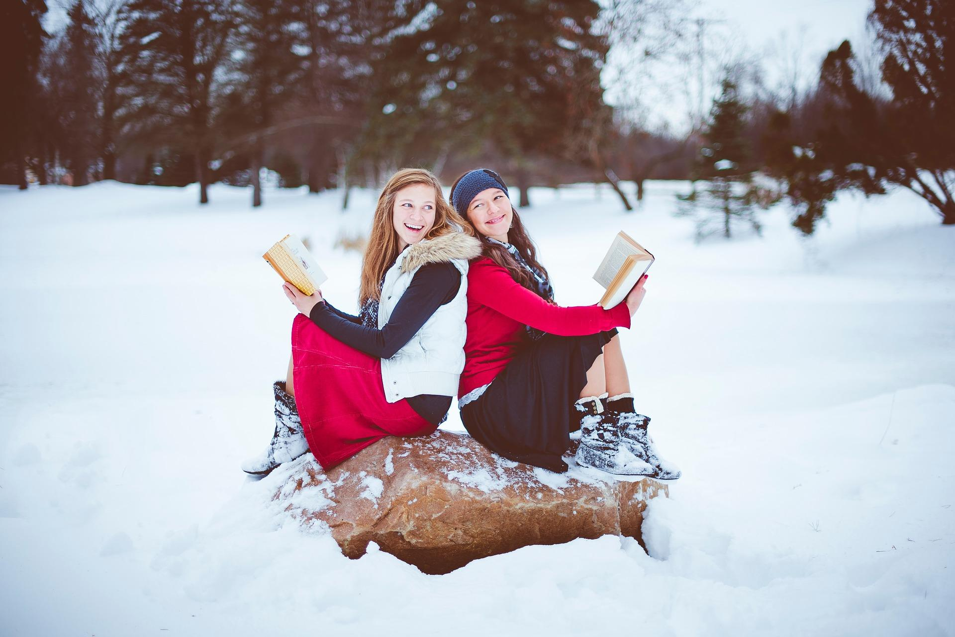 girls in snow reading